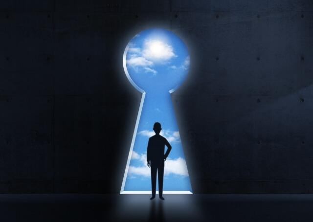 鍵穴から外をみるビジネスマン