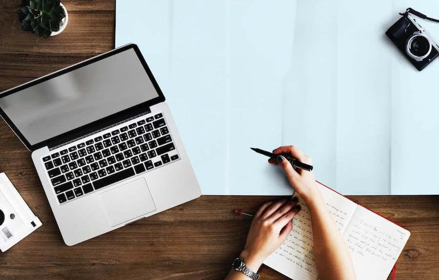 PCと机に広げた青い紙に書き込む人の手
