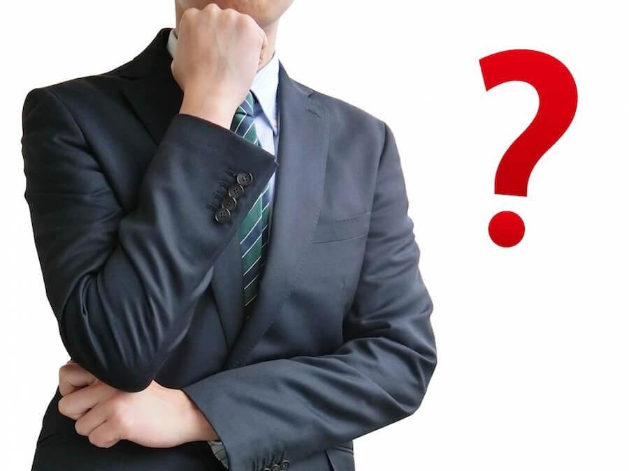 疑問を感じるスーツ姿の男性