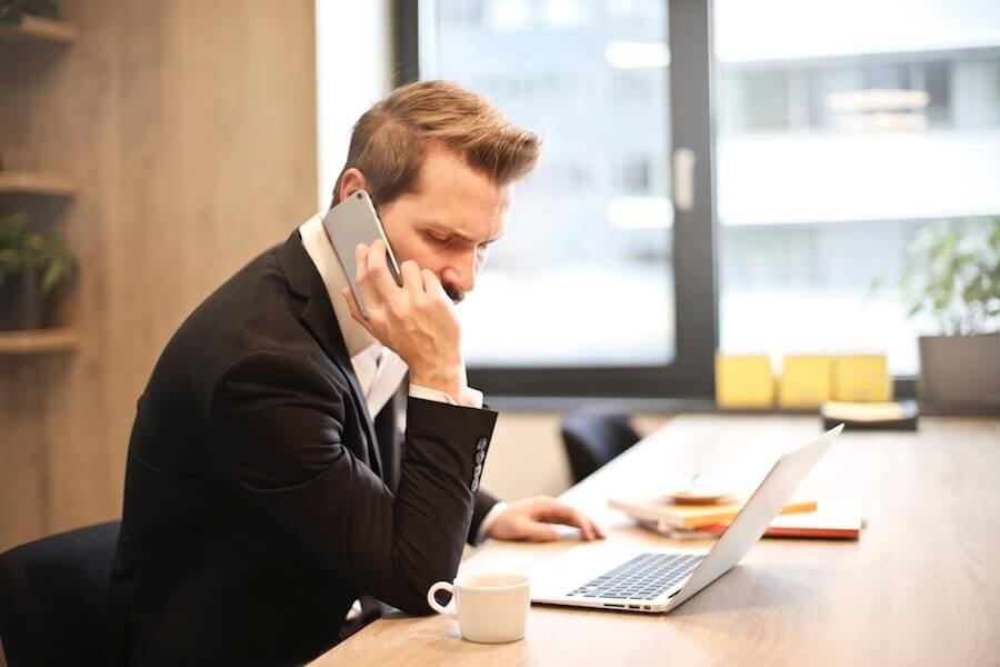 企業へ電話する男性