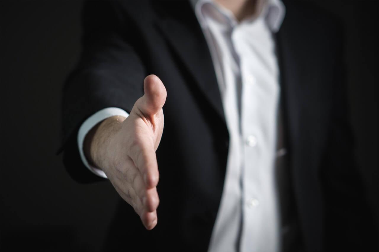 握手を差し出すスーツ姿のビジネスマン