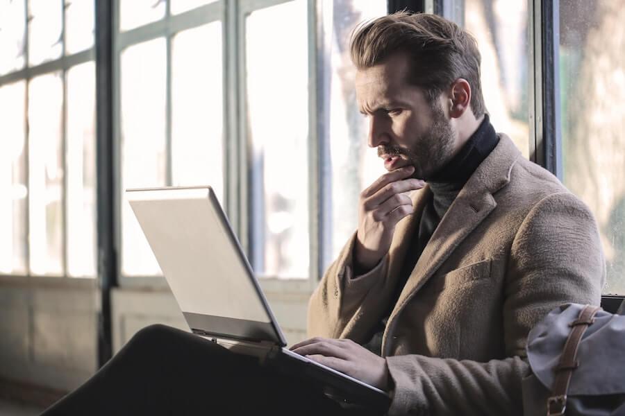 PCを見て悩むスーツの男性
