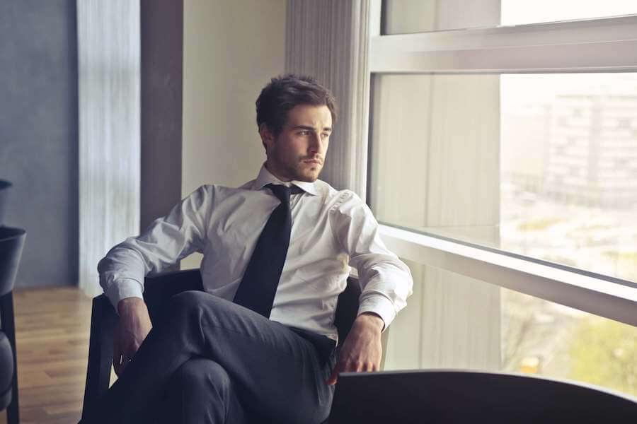 座って窓の外を眺める男性