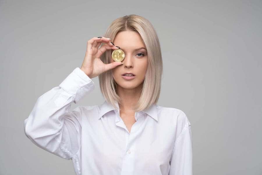 お金を目に当てる女性