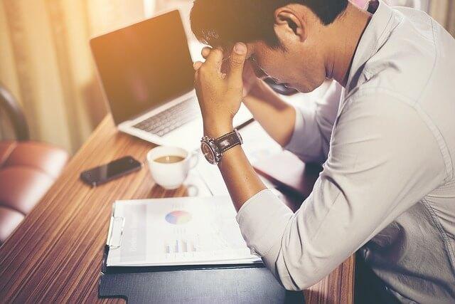 頭を抱える仕事中の男性