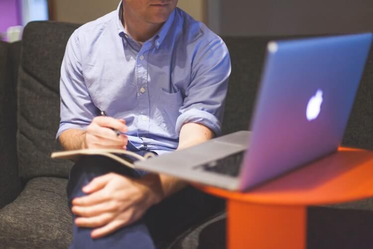 パソコンを眺めるワイシャツの男性