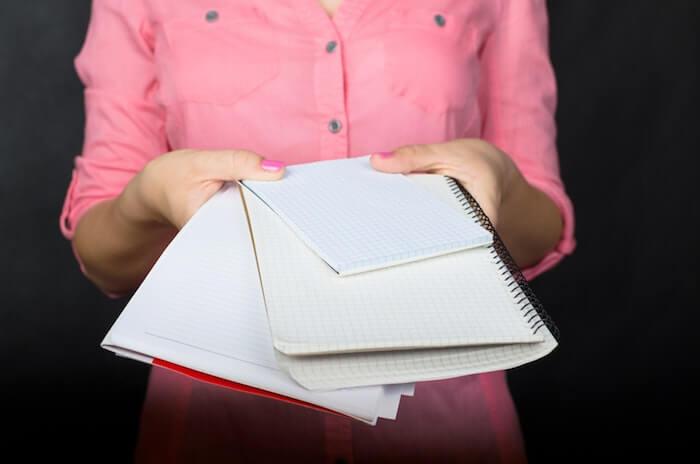 複数のノートを差し出す女性